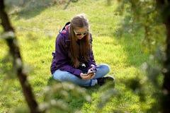 Chica joven que se sienta en la hierba con el teléfono móvil Imágenes de archivo libres de regalías