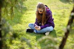 Chica joven que se sienta en la hierba con el teléfono móvil Fotografía de archivo libre de regalías