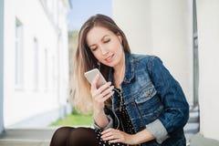 Chica joven que se sienta en la música que escucha de la yarda del campus de la universidad Fotos de archivo