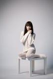 Chica joven que se sienta en la pequeña tabla Imagen de archivo libre de regalías