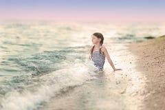 Chica joven que se sienta en la playa Foto de archivo libre de regalías