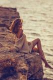 Chica joven que se sienta en la playa después de puesta del sol en el fondo del mar Imágenes de archivo libres de regalías