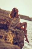 Chica joven que se sienta en la playa después de puesta del sol en el fondo del mar Imagen de archivo libre de regalías