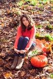 Chica joven que se sienta en la tierra cubierta con las capas delgadas otoñales secas Foto de archivo