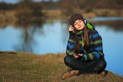 Chica joven que se sienta en la tierra y la música que escucha después de alza Fotografía de archivo libre de regalías