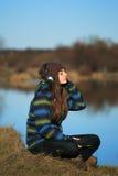 Chica joven que se sienta en la tierra y la música que escucha después de alza Imagen de archivo