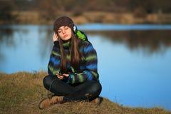 Chica joven que se sienta en la tierra y la música que escucha después de alza Imagen de archivo libre de regalías