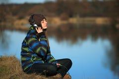 Chica joven que se sienta en la tierra y la música que escucha después de alza Fotografía de archivo