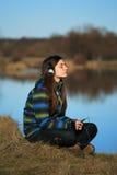 Chica joven que se sienta en la tierra y la música que escucha después de alza Fotos de archivo libres de regalías
