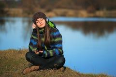 Chica joven que se sienta en la tierra y la música que escucha después de alza Foto de archivo