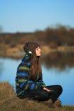 Chica joven que se sienta en la tierra y la música que escucha después de alza Imagenes de archivo