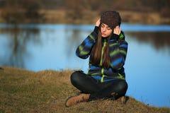 Chica joven que se sienta en la tierra y la música que escucha después de alza Foto de archivo libre de regalías