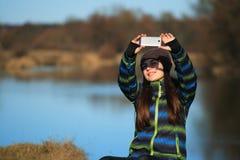 Chica joven que se sienta en la tierra y que se relaja con el libro Imagen de archivo libre de regalías