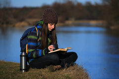 Chica joven que se sienta en la tierra y que se relaja con el libro Foto de archivo