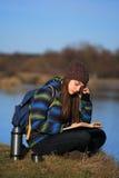 Chica joven que se sienta en la tierra y que se relaja con el libro Foto de archivo libre de regalías