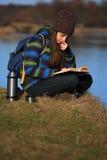 Chica joven que se sienta en la tierra y que se relaja con el libro Fotografía de archivo libre de regalías