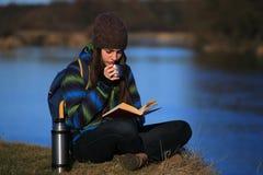 Chica joven que se sienta en la tierra y que se relaja con el libro Imagen de archivo