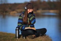 Chica joven que se sienta en la tierra y que se relaja con el libro Fotografía de archivo