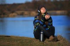 Chica joven que se sienta en la tierra y que se relaja con el libro Imagenes de archivo