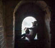 Chica joven que se sienta en la ventana Imágenes de archivo libres de regalías
