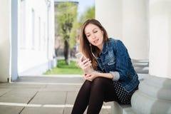 Chica joven que se sienta en la yarda del campus de la universidad que escucha la música Imagen de archivo libre de regalías