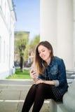 Chica joven que se sienta en la yarda del campus de la universidad que escucha la música Fotografía de archivo