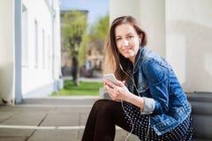 Chica joven que se sienta en la yarda del campus de la universidad que escucha la música Foto de archivo libre de regalías
