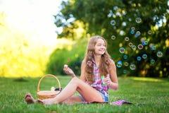 Chica joven que se sienta en las burbujas que soplan de la hierba Fotos de archivo
