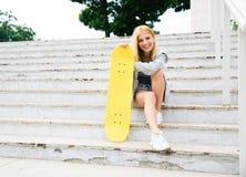 Chica joven que se sienta en las escaleras con el monopatín Imagenes de archivo