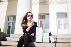 Chica joven que se sienta en los pasos con los panieres Foto de archivo