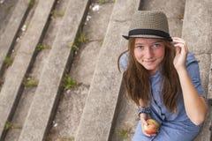 Chica joven que se sienta en los pasos de piedra del parque viejo Sonrisa Imágenes de archivo libres de regalías