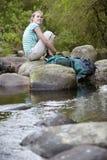 Chica joven que se sienta en piedras de Forest Stream Imagen de archivo libre de regalías