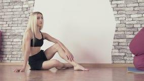 Chica joven que se sienta en piso en estudio de la danza Reclinación bastante femenina después de danza metrajes
