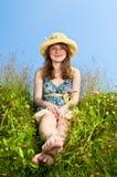 Chica joven que se sienta en prado Imagenes de archivo