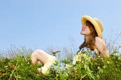 Chica joven que se sienta en prado Imagen de archivo libre de regalías