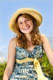 Chica joven que se sienta en prado Foto de archivo libre de regalías
