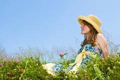 Chica joven que se sienta en prado Imagen de archivo