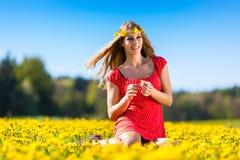 Muchacha en primavera en un prado de la flor con el diente de león fotografía de archivo