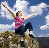 Chica joven que se sienta en roca Foto de archivo