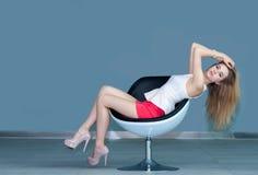 Chica joven que se sienta en silla y que toca su pelo Fotografía de archivo libre de regalías
