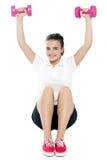 Chica joven que se sienta en suelo y que hace ejercicio Imagen de archivo libre de regalías