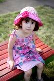 Chica joven que se sienta en un banco Fotografía de archivo