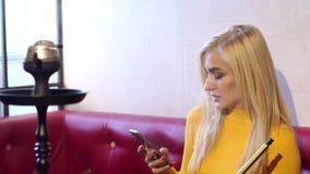 Chica joven que se sienta en un café en un sofá rojo con un teléfono y una cachimba almacen de metraje de vídeo