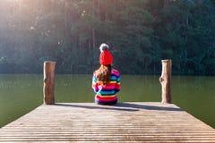 Chica joven que se sienta en un embarcadero Imagenes de archivo