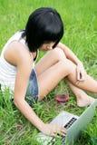 Chica joven que se sienta en un parque con el ordenador portátil Fotografía de archivo libre de regalías