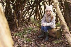 Chica joven que se sienta en un refugio del bosque hecho de ramas de árbol Imagen de archivo