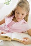 Chica joven que se sienta en un sofá que lee un libro Fotos de archivo libres de regalías