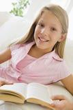 Chica joven que se sienta en un sofá que lee un libro Imagen de archivo libre de regalías