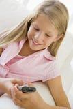 Chica joven que se sienta en un sofá Texting Fotos de archivo libres de regalías