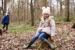 Chica joven que se sienta en un tocón de árbol en un bosque Imágenes de archivo libres de regalías